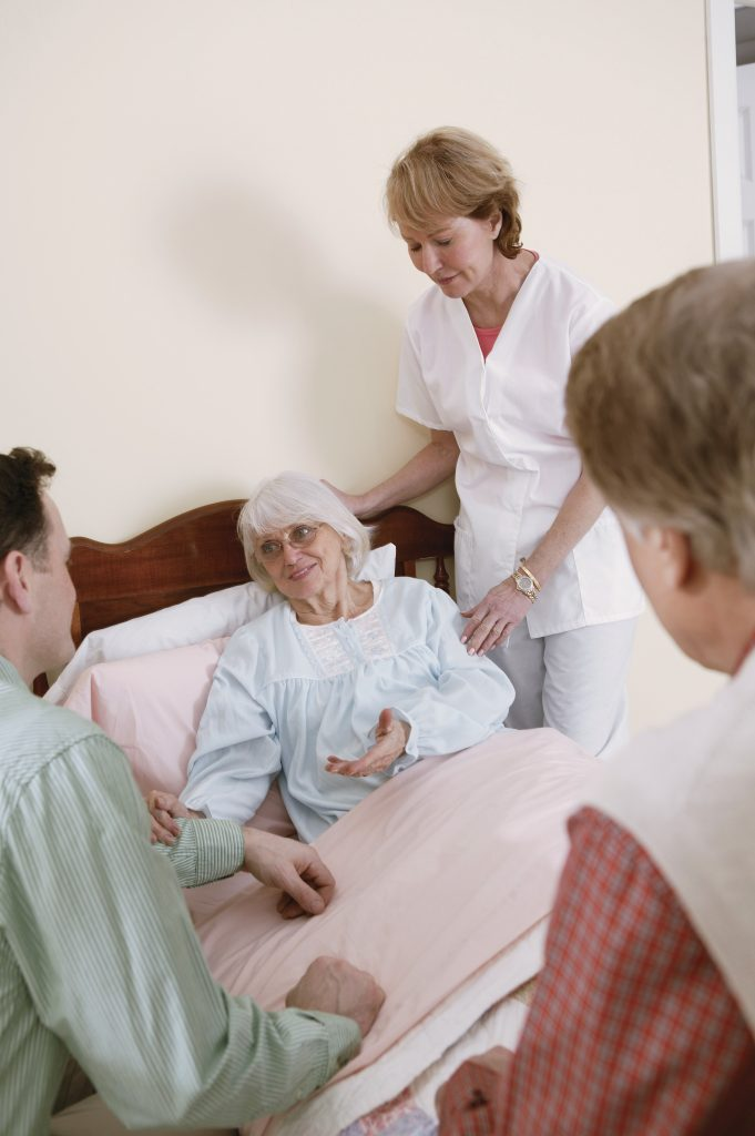 An elderly with caregiver visited by relatives